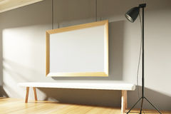 Blank picture frame in sunny empty room with wooden bench Stock Photos