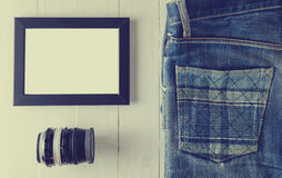 Blank Picture frame with vintage camera lens and Jean. Royalty Free Stock Image