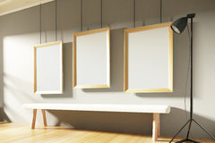 Blank picture frame with white wooden bench in empty room at sun Royalty Free Stock Photos