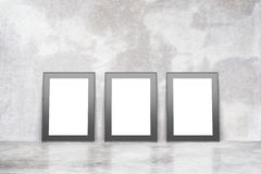Blank picture frames on concrete floor in empty loft room. L, mock up Stock Images