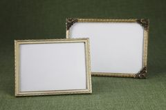 Blank picture frames, gold. Blank picture frames against green background Royalty Free Stock Photos