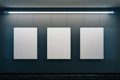 Blank picture frames on grey wall with glowing lamp. Mock up Stock Photography