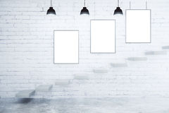 Blank picture frames on white brick wall, lamps and stairs Royalty Free Stock Photos