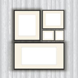 Blank picture frames on a wooden wall background Stock Photos