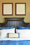 Blank pictures on wall above bed. Two blank pictures on the wall above a comfy bed with blue bedding and pillows Royalty Free Stock Photography