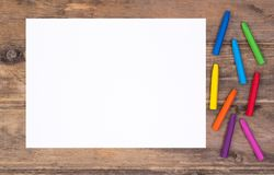 Blank piece of paper with colorful crayons on kid`s desk. Top view with copy space royalty free stock photos