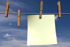 Blank piece of paper hanging on a rope. Blank piece of paper hanging on a clothesline Royalty Free Stock Image