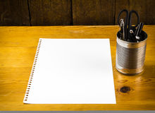 Blank piece of paper on wood table with pens in metal can Royalty Free Stock Photography