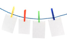 Blank pieces of paper and colored clothespins Royalty Free Stock Images