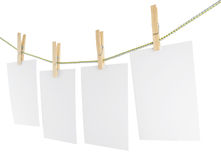 Blank pieces of paper and wooden clothespins Stock Photo