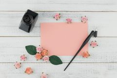 Blank pink card, oblique pen and bottle of ink. Decorate with pink rose paper flowers on white wood background Royalty Free Stock Photos