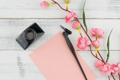 Blank pink card, oblique pen and bottle of ink. Decorated with fake pink flower branches on white wood background Royalty Free Stock Photography
