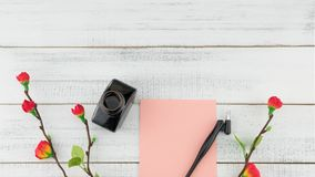 Blank pink card, oblique pen and bottle of ink decorated with fake red flower. Branches on white wood background with copy space Stock Image