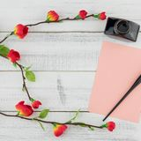 Blank pink card, oblique pen and bottle of ink. Decorated with fake red flower branches on white wood background with copy space Royalty Free Stock Photography