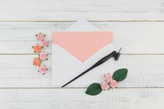Blank pink card in white envelope and oblique pen. Decorate with pink rose paper flowers on white wood background with copy space Royalty Free Stock Photo