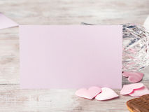 Blank pink invitation for romantic date. Empty pink paper note with two stemmed champagne glasses pink hearts and chocolate cookies on wooden textured background Stock Photo