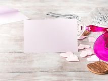 Blank pink invitation for romantic date. Empty pink paper note with two stemmed champagne glasses pink hearts and chocolate cookies on wooden textured background Royalty Free Stock Images