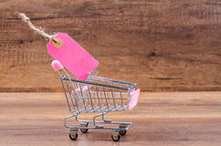 Blank pink paper price tag with shopping cart. Stock Photos