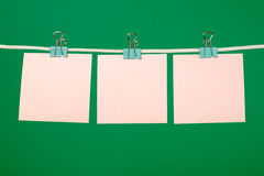 Blank pink paper sheets hanging on string Royalty Free Stock Photo