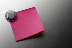 Blank pink stickie. Note tacked onto metal surface with magnet Stock Images