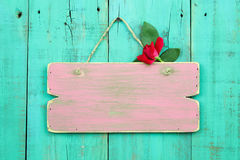 Blank pink weathered sign with red flower hanging on antique green wood door Royalty Free Stock Photo