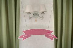 Blank pink wedding plate in the form of ribbons hanging on the w Royalty Free Stock Image