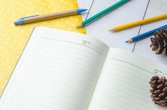 Blank daily planner notebook with pen and color pencils Stock Images