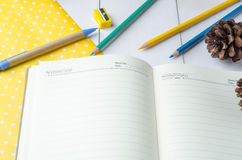 Blank daily planner notebook with pen and color pencils Royalty Free Stock Photos
