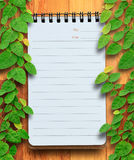 Blank planning notebook on wood background with ivy fixing tree. Stock Photography