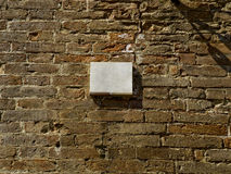 Blank plaque on a brick wall surface. Royalty Free Stock Images