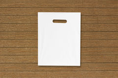 Blank plastic bag mock up on wooden floor. Empty white polyethylene package mockup. Consumer pack ready for logo design or. Identity presentation. Commercial stock photo