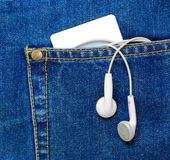 Blank plastic card and earphones in a jeans pocket. Stock Image