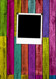 Blank Polaroid on Colorful Wooden Background. A blank instant photo on multi-colored wooden planks background. A great frame for your images. Please visit my Stock Photography