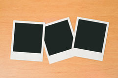 Blank polaroid frames. On wooden background Royalty Free Stock Photography
