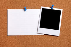 Blank polaroid photo frame, cork notice board, white index card, copy space. Blank photo print and office index card pinned to a cork notice board. Space for royalty free stock photos