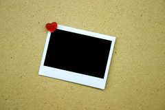 Blank polaroid pinned on wall. A picture of a blank polaroid pinned to the wall with a heart-shaped push pin royalty free stock photography