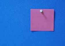 Blank post-it. A blank purple purple post-it on blue synthetic corkboard stock image