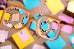 Blank post-its seen through high diopter eyeglasses. Royalty Free Stock Photos
