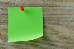 Blank Post it Note. Green post it note with red push pin on a wooden background Royalty Free Stock Photo