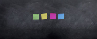 Blank Post It notes on board. 4 blank post it notes are stuck to the blackbaord stock photo