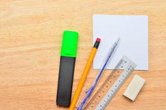 Blank post-it with pen, pencil, ruler, highlight market and eraser on office wooden table. Above view stock images