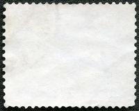 Blank postage stamp on a black background Stock Photos