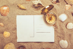 Blank postcard in hot beach sand and compass. Blank postcard in hot beach sand and magnetic compass with some sea shells, copy space for summer holiday vacation stock photography