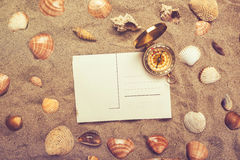 Blank postcard in hot beach sand and compass. Blank postcard in hot beach sand and magnetic compass with some sea shells, copy space for summer holiday vacation royalty free stock photo