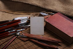 Blank postcard, red book and paint brushes on jute Royalty Free Stock Images