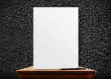 Blank poster frame on wood table at black stone wall,perspective Royalty Free Stock Photo