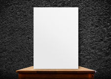 Blank poster frame on wood table at black stone wall,perspective Royalty Free Stock Photography