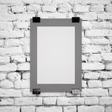 Blank poster hanging in a frame on a background of white painted brick wall Royalty Free Stock Photography