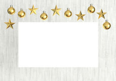 Blank poster with hanging golden balls and stars ornaments on white wooden background Stock Images