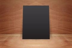 Blank poster stand on a wooden background. Blank black  poster stand on a wooden background Stock Photo